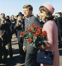 Mrs. Kennedy wore a vibrant pink Chanel suit with matching pillbox hat