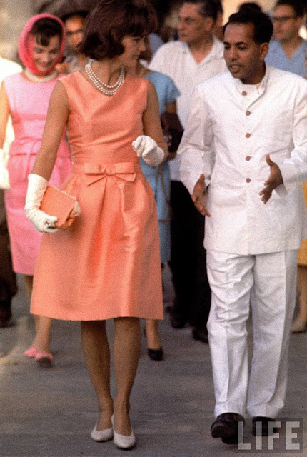 Jackie Kennedy at the Palace of the Maharajah in Udaipur, India during a state visit, wearing a fitted silk apricot dress by designer Oleg Cassini.