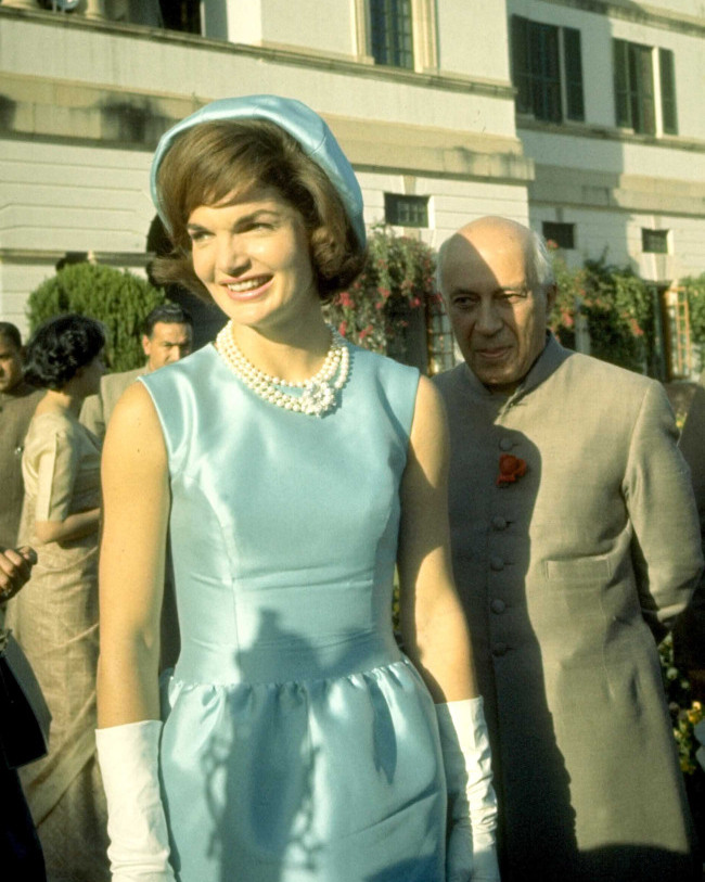 First Lady Jackie Kennedy in blue dress and hat walking with Indian Prime Minister Jawarhalal Nehru in the garden of his residence in New Delhi.